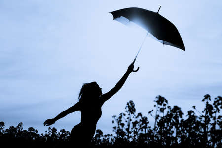 Unplugged free silhouette woman with umbrella up to blue sky. Nature girl at windy rainy day has adventure wanderlust. Wonderful scene of imagination power and departure to new horizons in youth.