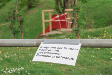 Corona virus quarantine lockdown prohibit playground slide. Covid-19 safety prevention. Closure prohibition sign. German text mean closed because of coronavirus restriction regulation! Keep off!