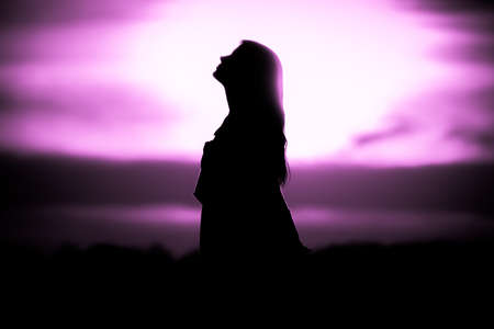 Youth woman soul at pink sun meditation dreaming past times. Silhouette in front of sunset or sunrise in summer nature. Symbol for healing burnout therapy, wellness relaxation or resurrection.