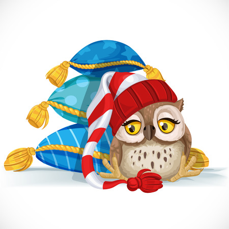 Cute owlet in a cap sits near a pile of pillows and wants to sleep