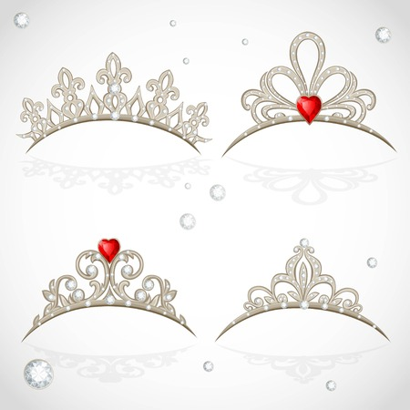 object complement: Set openwork jewelry tiaras with diamonds and faceted red stones in a heart shape on white background
