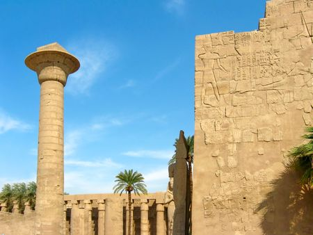 thebes: Single enormous column and wall with relieves in peristyle courtyard in the Temple of Amun-Ra at Karnak. Antique Thebes. Luxor, Egypt.