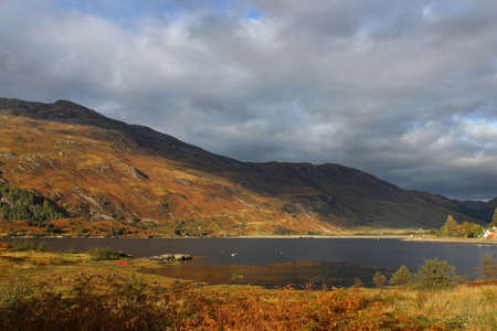 Loch surrounded by autumn mountains