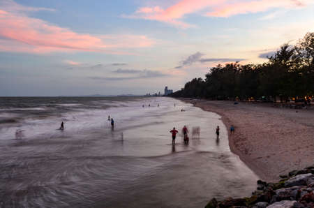 crema: A lot of people on the beach in crema moving fast at dusk.
