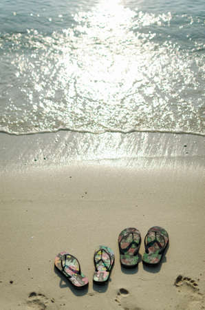 pairs: Two pairs of sandals on the beach.