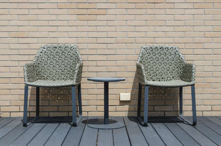 two chairs: Two chairs by the swimming pool. Behind a brick wall