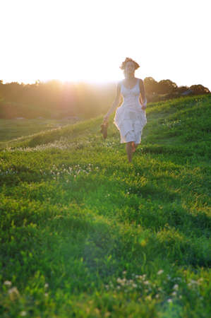 runing: Girl runing on a green summer meadow on a sunny summer day. Stock Photo
