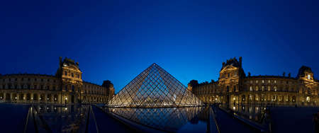 Panoramic Musee de Louvre Pyramid glowing at dusk, Paris