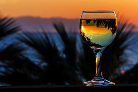 white wine on the sunset sea background in april