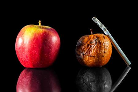 twee appels en een sigaret in zwarte achtergrond Stockfoto