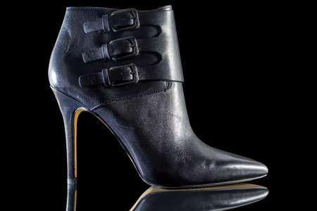 leather background: Black high heel shoes for women in isolated black background