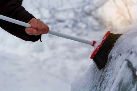 closeup of man cleaning snow from car in winter