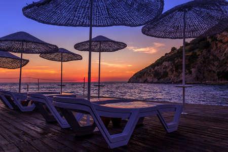 sunbeds: sunbeds and umbrellas at sunset in summer
