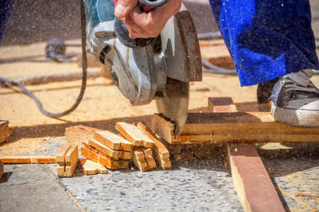 electric saw: Carpenter using an electric saw cutting small wooden figures