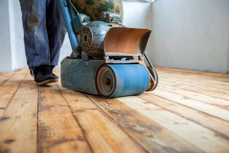 Trabajador de pulido piso de parquet con rectificadora Foto de archivo