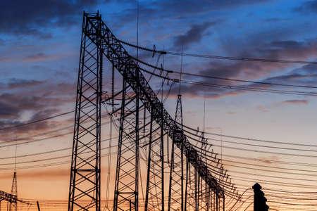energia electrica: Estación de energía eléctrica al atardecer con cielo dramático