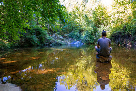 man meditating: man meditating in the lake on stone in the summer