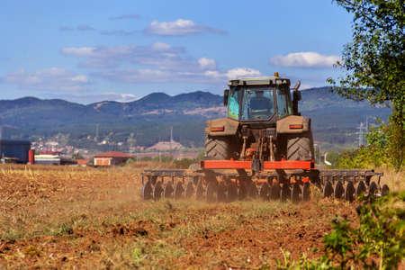 siembra: Campo de arar tractor rojo Foto de archivo