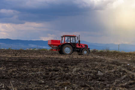 Tractor spreading artificial fertilizers in spring