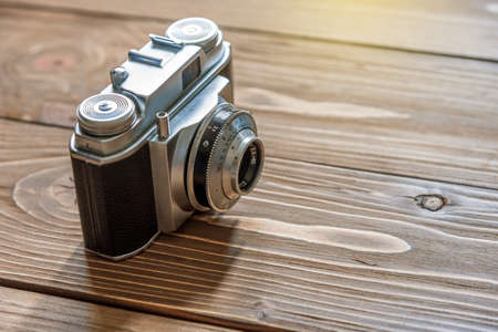 old photograph: Retro photo camera on wooden background