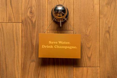 Houten achtergrond met plaat. Bespaar water. Drink Champagne.Concept voor de verkoop van hout