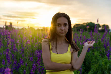 lupines: beautiful girl in yellow dress  standing in a field of lupine flowers