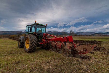 Tractor plowing fields. Preparing land for sowing in autumn. 스톡 콘텐츠