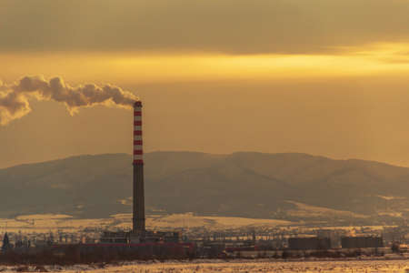 Smoke out from the pipe at the factory, in winter, at sunset. Stock Photo