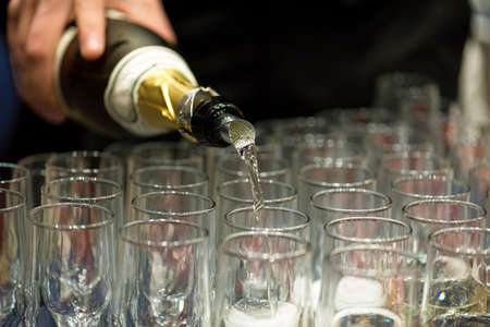 Bartender pouring champagne into glasses at party.