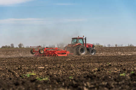 Tractor plowing fields. Preparing land for sowing in autumn. Stock Photo