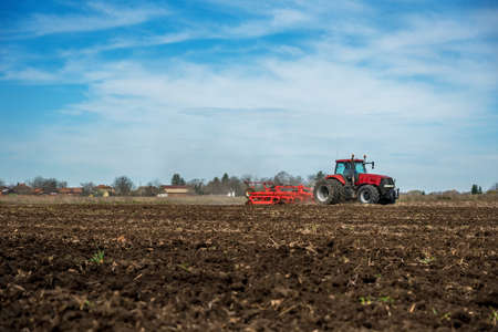 Farmer in tractor preparing land with seedbed cultivator. 写真素材