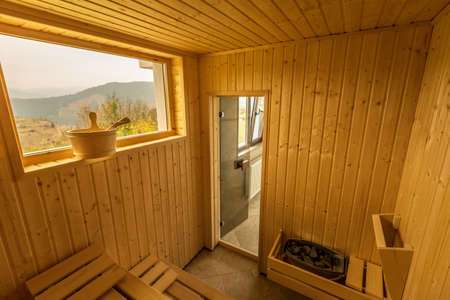 Wooden sauna with seats. Accessories interior of sauna spa.