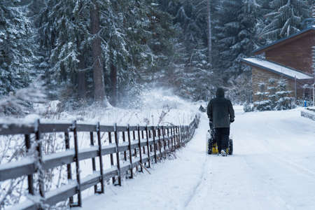 Man clears snow with snow blower, winter snowfall. Reklamní fotografie