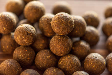 Carp fishing. Different of carp boilies and accessories for carp fishing isolated on wooden