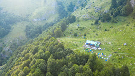 Rai hut surrounded with fresh green mountain pastures with blooming flowers. Banco de Imagens - 129810639