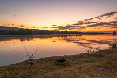 Carp fishing rods with carp bite indicators and reels set up on rod pod near lake river. Fishing during sunrise.