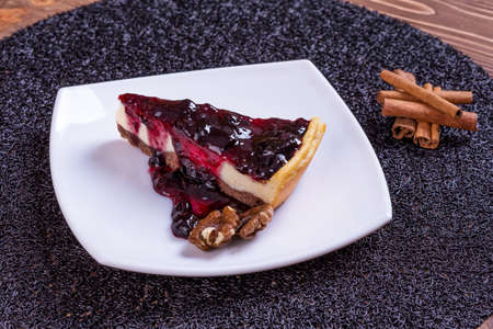 Piece of blueberry cheesecake on a plate with a silver fork.