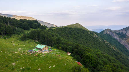 Rai hut surrounded with fresh green mountain pastures with blooming flowers.