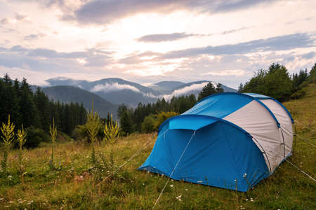 Landscape scenery of camping tent on grass field with  of forest and mountains and sunset sky in natural park.