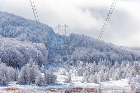 Electricity pylons in winter mountains in Bulgaria.