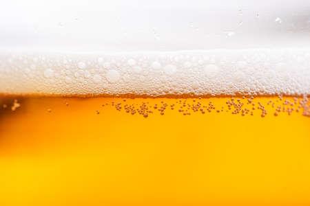 Helles Bier mit Blasen und Schaumhintergrund. Bier sprudelt Textur hautnah.