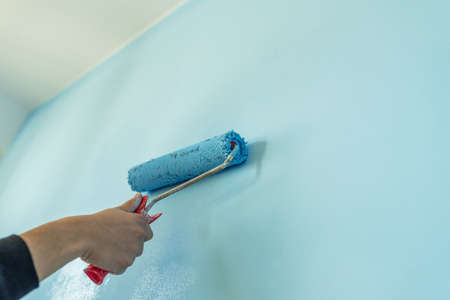 Decorator's hand painting wall with roller.
