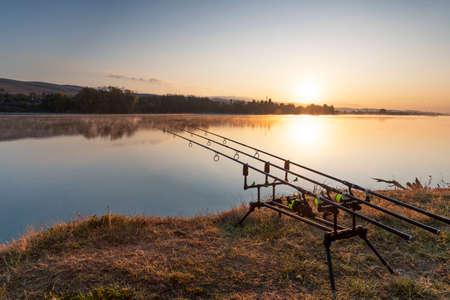 Carp fishing rods with carp bite indicators and reels set up on rod pod near lake river.
