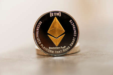 Golden Etherium coin close up. Ether is a cryptocurrency whose blockchain is generated by the Ethereum platform. Standard-Bild
