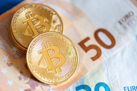 Close up of Gold Bitcoin on euro currency background. Conceptual photo.
