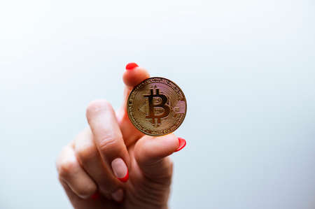 Cryptocurrency golden bitcoin coin in woman hand - symbol of crypto currency - electronic virtual money.