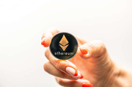 Golden Ethereum in a woman hand, Digital symbol of a new virtual currency. Standard-Bild