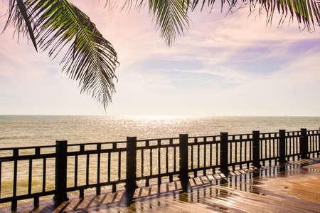 Hölzerne Terrasse auf dem Strand, der zum funkelnden Meer, Wellen, goldener Himmel eines sonnigen Tages schaut.