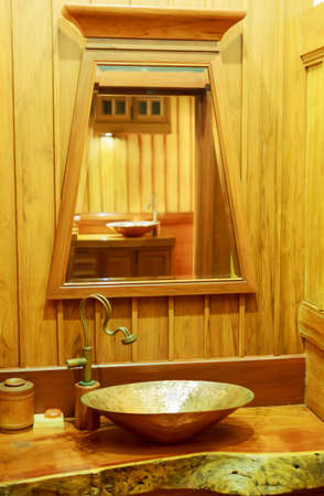 wash basin: Vintage brass wash basin and faucet in wooden bathroom.