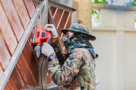 A worker use electric sander on wooden door